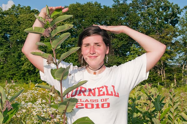 Photo of Undergraduate as she compares her height to the height of a plant