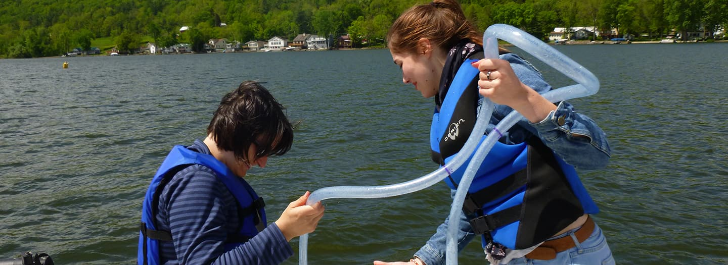 Two students on a boat conducting field research