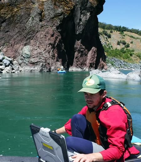 Liam Zarri, a grad student, on a boat at Eel River Lake searching for sturgeons