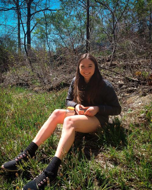 Undergraduate student, Raisa Kochmaruk shown sitting down on a hillside