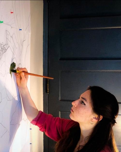 Undergraduate student, Raisa Kochmaruk shown painting artwork on a wall